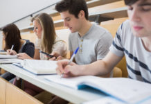 Students sitting at the desk at the lecture hall taking notes